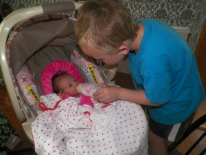 Buck enjoyed being a big cousin and feeding her a bottle.